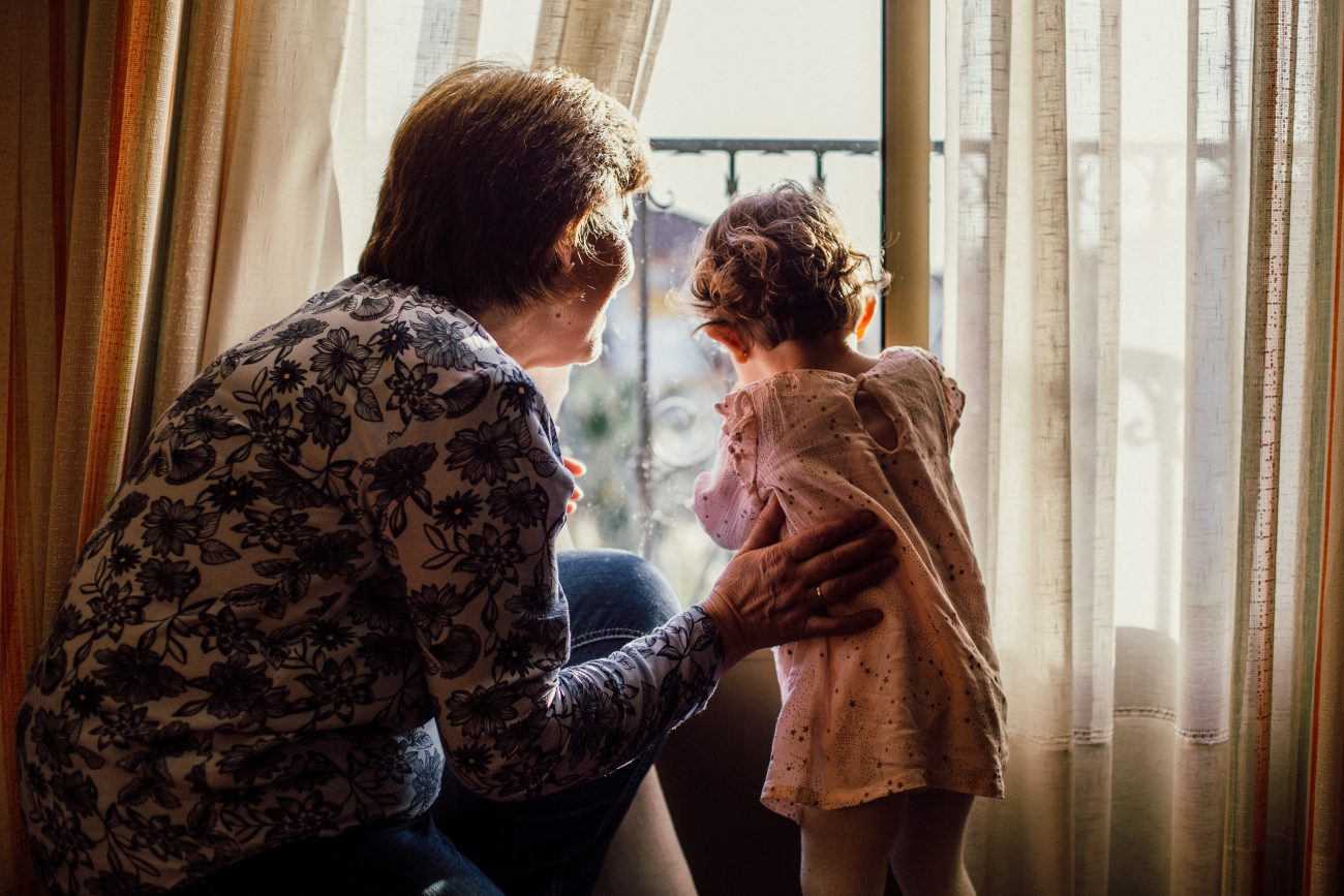 stop-ageism-woman-holding-baby-near-window