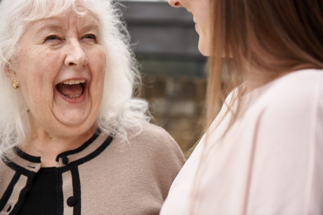 Older woman and younger girl laughing